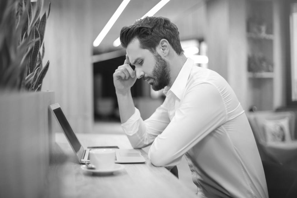 mężczyzna zastanawia się jak napisać wniosek o odrzucenie odziedziczonych długów w spadku